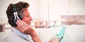 Man listening to music on headphones in living room Royalty Free Stock Image