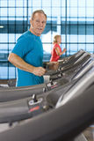 Man listening to music on headphones and running on treadmill in health club Stock Images