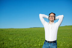 Free Man Listening To Music In A Green Field Royalty Free Stock Image - 31286436