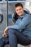Man Listening To Music At Laundromat Royalty Free Stock Photo