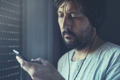 Man listening to music on mobile phone with headphones Royalty Free Stock Image