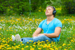 Man listening to music outdoors. Portrait of a relaxed young man sitting on grass in park and listening to music on headphone royalty free stock photography