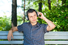 Man listening to music outdoors. Portrait of a relaxed young man sitting on bench in park and listening to music on headphone Stock Image
