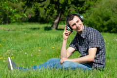 Man listening to music outdoors. Portrait of a relaxed young man sitting on grass in park and listening to music on headphone stock photo