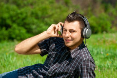 Man listening to music outdoors. Portrait of a relaxed young man sitting on grass in park and listening to music on headphone Stock Image