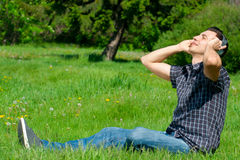 Man listening to music outdoors. Portrait of a relaxed young man sitting on grass in park and listening to music on headphone stock photos