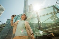 Travel and lifestyle concept. Man listening to music on phone and dancing against the background of skyscrapers. Stock Photography