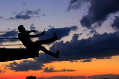 Man is listening to music on roof. Clouds and sunset Stock Images