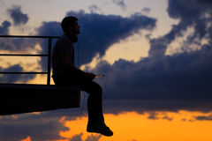 Man is listening to music on roof. Clouds and sunset Stock Image