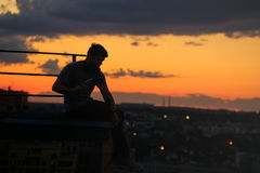 Man is listening to music on roof. Clouds and sunset Stock Photo