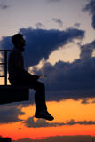 Man is listening to music on roof. Clouds and sunset Stock Photography