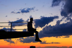 Man is listening to music on roof. Clouds and sunset Stock Photos