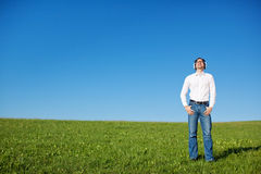 Man listening to music in a sunny green field Royalty Free Stock Photos