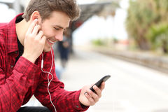 Man listening to the music waiting in a train station Royalty Free Stock Photos