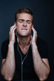 Man is listening to music on white earphones. In black v-neck shirt on dark background Royalty Free Stock Images