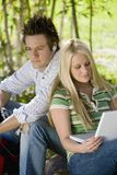 Man Listening To Music While Woman Using Laptop. Young men listening to music while women using laptop in college campus Stock Photo