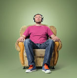 Man listening to relaxing music while sitting in a chair. On green background Stock Image