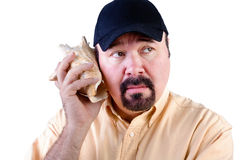 Man listening to sound of sea in shell Stock Photos