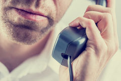 Man listening to a telephone conversation. Close up of the mouth and chin of an unshaven man listening to a telephone conversation holding the receiver in his Stock Image