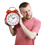 Man listening to the ticking of alarm clock Royalty Free Stock Photos
