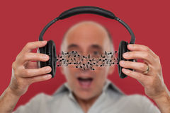 Man listening and visualizing music notes. Man listening and visualizing music from headphones Stock Images