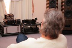 Man listens music from turntable. The Man listens music from turntable Royalty Free Stock Photography