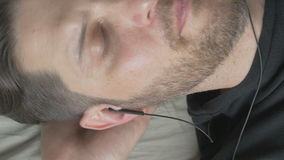 A man listens to music with headphones, top view stock video footage