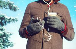 Man listens to music on a smartphone drinks coffee over christmas. Tree background Royalty Free Stock Photo