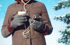 Man listens to music on a smartphone holds coffee cup in hand. On a christmas tree background Royalty Free Stock Photo