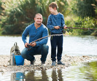 Man and little boy fishing. Glad adult men and little boy spending time outdoors and fishing Stock Photo