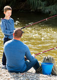 Man and little boy fishing. Happy young men and little boy spending time outdoors and fishing Stock Photography