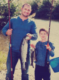 Man and little boy fishing Stock Images