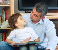 Man and little boy reading book. Man and little boy sitting on the floor in living room and reading book Royalty Free Stock Photos