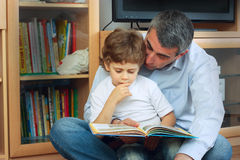 Man and little boy reading book. Man and little boy sitting on the floor in living room and reading book Royalty Free Stock Images