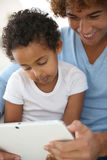 Man with little boy using tablet Stock Photography