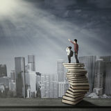 Man with little child standing on books stack Stock Photo