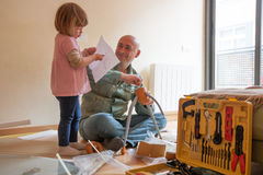 Man and little girl assembling coffee table stock images