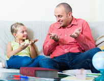 Man and little girl with books indoors. Adult tutor and cute little girl discussing with books in domestic interior Royalty Free Stock Photo