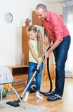 Man and little girl hoovering at home Royalty Free Stock Images