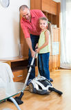 Man and little girl hoovering at home Royalty Free Stock Photos