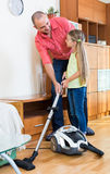Man and little girl hoovering at home Stock Images