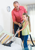 Man and little girl hoovering at home Stock Photos