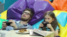 Man little girl playing video game, gaming habit, entertainment stock footage