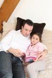 Man an little girl reading book Stock Image