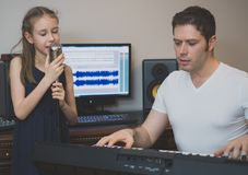Man with little girl rehearsing song. Man with little girl rehearsing song in music studio Stock Photo