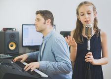 Man with little girl rehearsing song. Man with little girl rehearsing song in music studio. Focused on girl Royalty Free Stock Images
