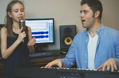Man with little girl rehearsing song. Man with little girl rehearsing song in music studio Stock Image