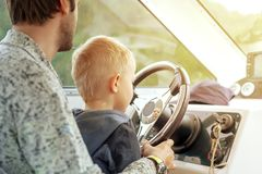 Man with little son driving boat royalty free stock photography