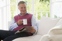 Man in living room with coffee reading newspaper Royalty Free Stock Image