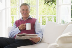 Man in living room with coffee reading newspaper Stock Image